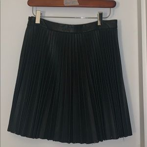 Pleated leather skirt with detailed cutouts